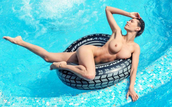 Девушка с короткой стрижкой голая плавает на круге