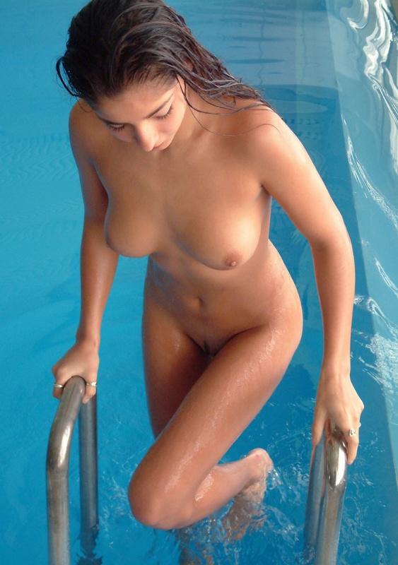 Обнаженная девушка с интимной прической выходит из бассейна