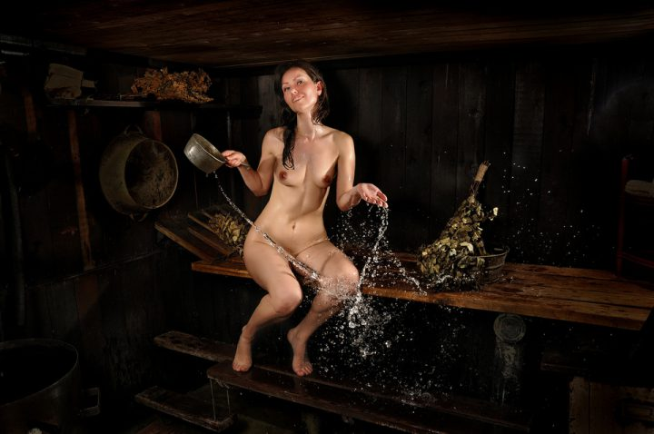 Веселая женщина сидит в бане и поливает себя водой