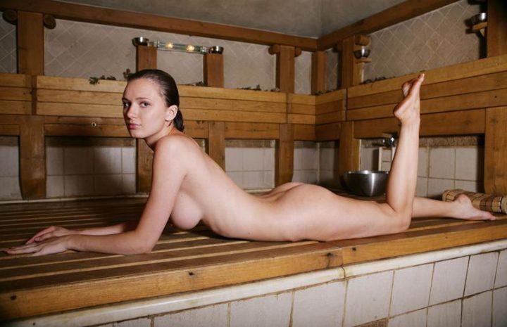 Молодая девушка на скамейке лежит в бане