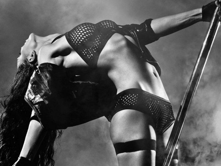 Сексуальная красотка в сетчатом костюме эротично танцует