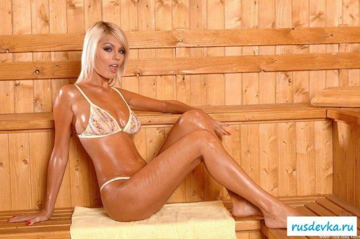 Девушка в купальнике мокрая от пота сидит в сауне