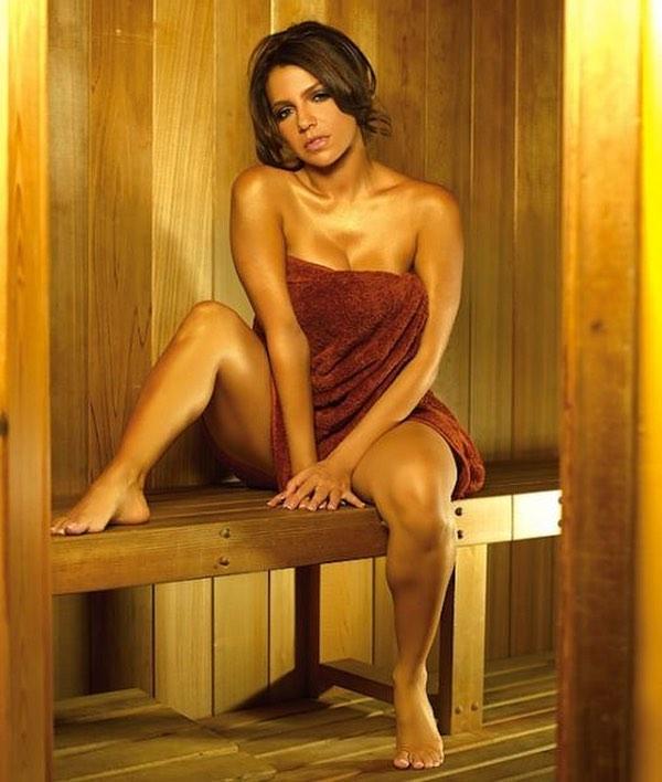 Девушка в полотенце сидит в сауне