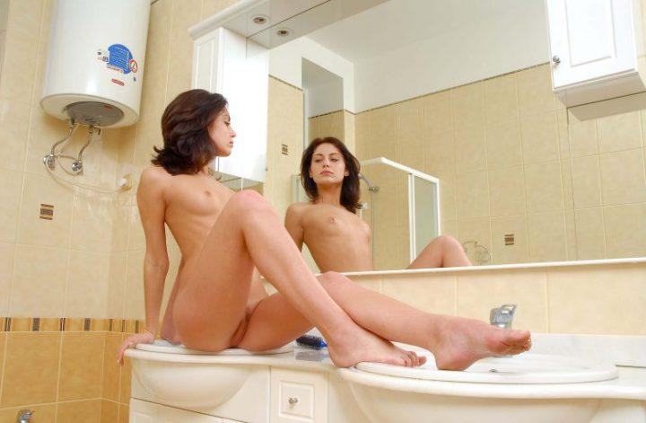 Красотка сидит на раковине без одежды и любуется собой в зеркале