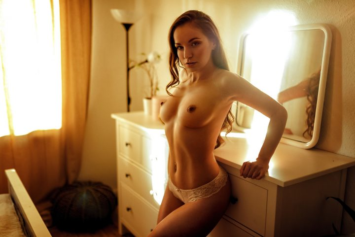 Молодая соблазнительница стоит у зеркала в своей комнате с голыми сиськами и в кружевных трусиках