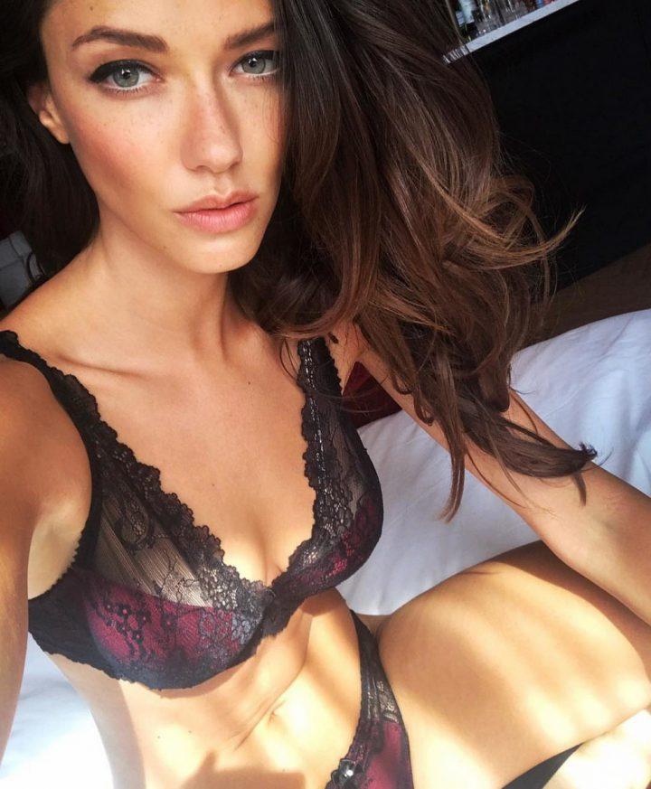 Красивая девушка с соблазнительными губами сидит на кровати в красивом белье