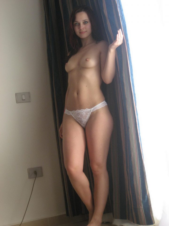 Яркая девушка без лифчика в одних трусиках стоит у закрытого окна