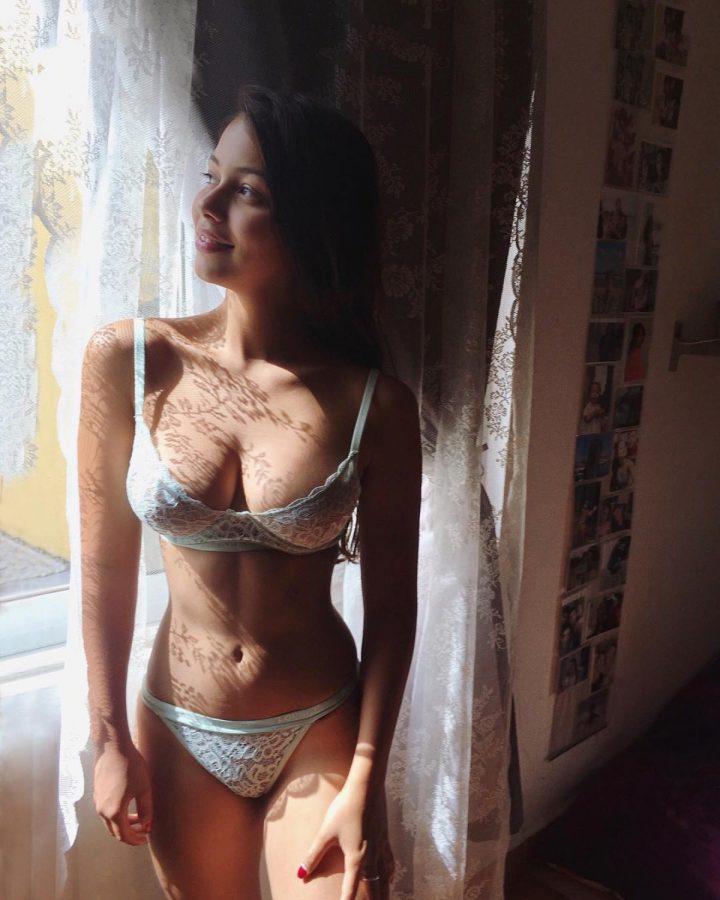 Юная красотка с большими сиськами в кружевном белье стоит у окна
