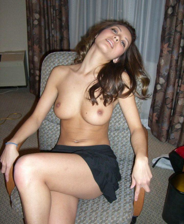 Молодая девушка сидит в кресле в одной юбке и с голыми красивыми сиськами