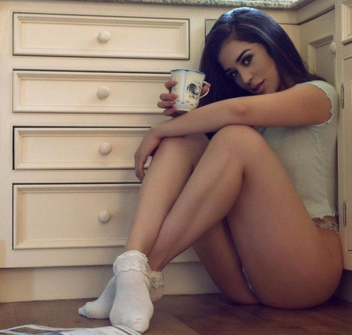 Красивая девушка в белых носочках сидит на полу красивой попкой и пьет чай