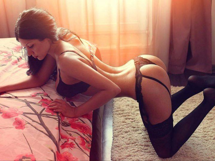 Сексуальная красивая девушка стоит на коленях облокотившись о кровать руками