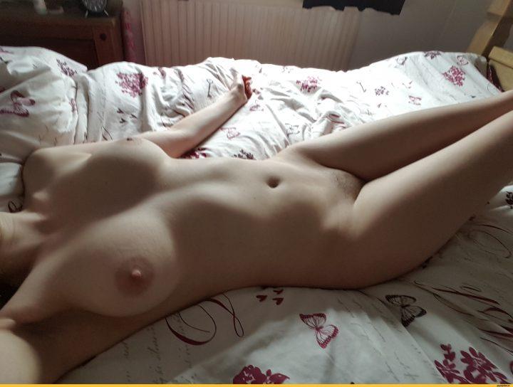 Девушка с красивыми  большими сиськами на кровати готова к сексу