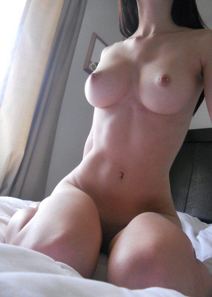 Девушка с длинными волосами сидит в кровати с упругими сиськами и пирсингом в сосках с тонкой талией и без трусиков