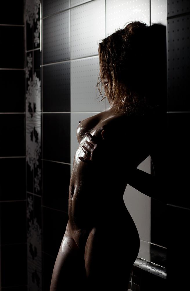 Сексуальная красотка в темноте стоит голая в ванной