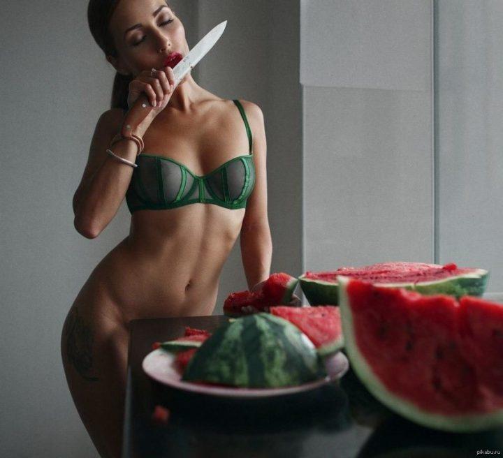 Сексуальная красотка в одном лифчике и без трусиков ест арбуз с ножа