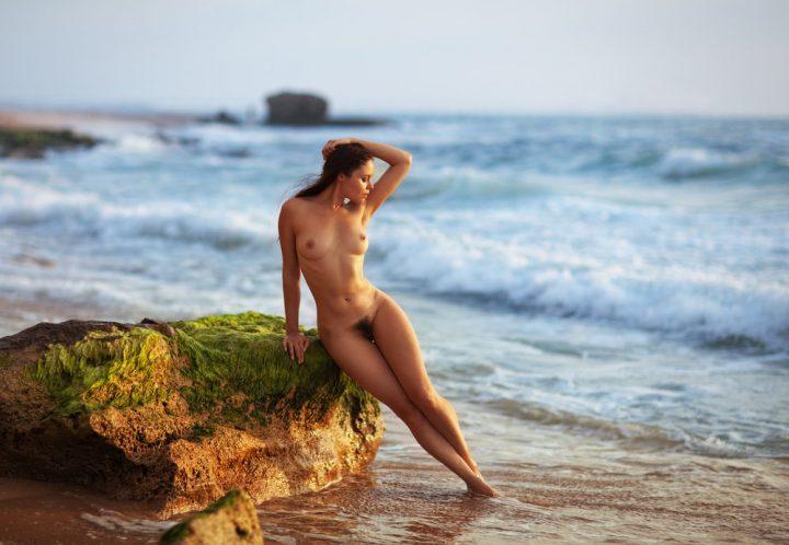 Стройная красотка без одежды стоит у камня на море
