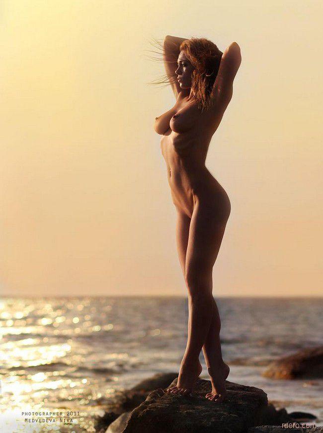 Стройная девушка с красивыми сиськами ходит на носочках у берега