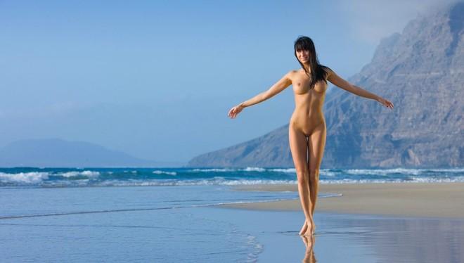 Приятная девушка с длинными ногами без одежды гуляет по берегу моря
