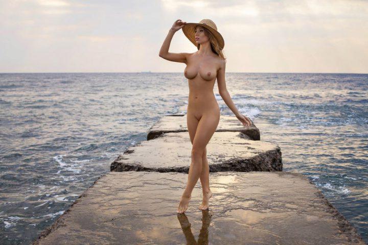 Женщина с красивыми формами в соломенной шляпе стоит на камнях