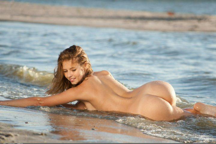 Длинноволосая девушка лежит на берегу моря с голой попой