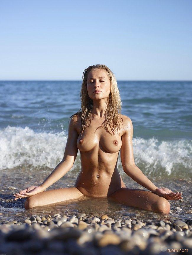 Милая девушка на берегу моря без одежды с закрытыми глазами медитирует