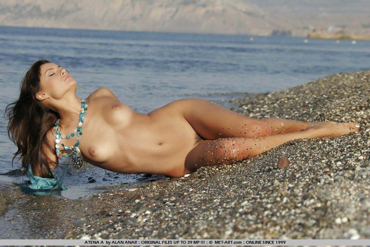 Девушка загорает голой на берегу моря