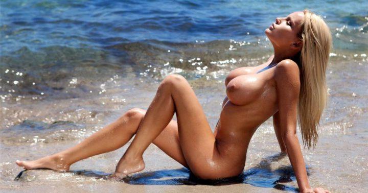 Красивая дамочка с сексуальной фигурой без одежды сидин на берегу моря