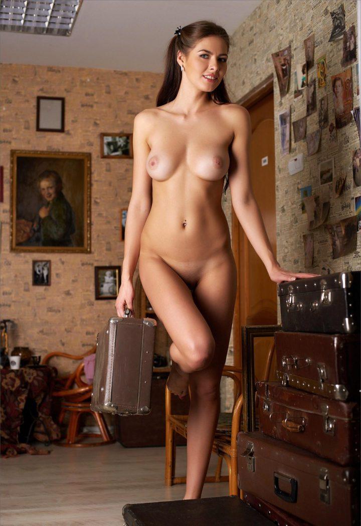 Девушка с милой улыбкой голая стоит в комнате с чемоданом в руках