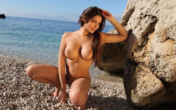 Голая девушка сексуально сидит на берегу моря