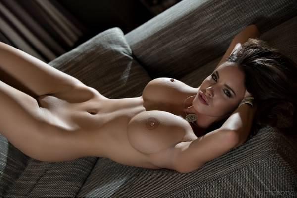 Брюнетка с пухлыми губами сексуально закинула ноги на диван