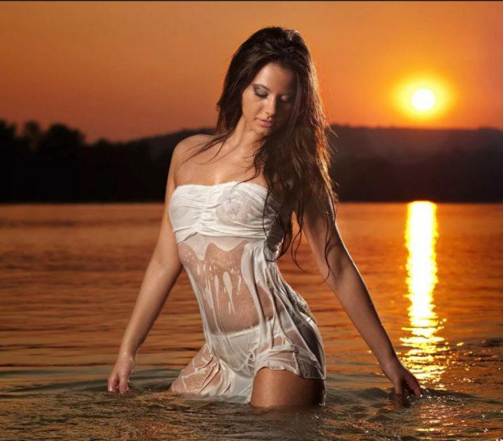 Девушка на закате купается в озере в одежде