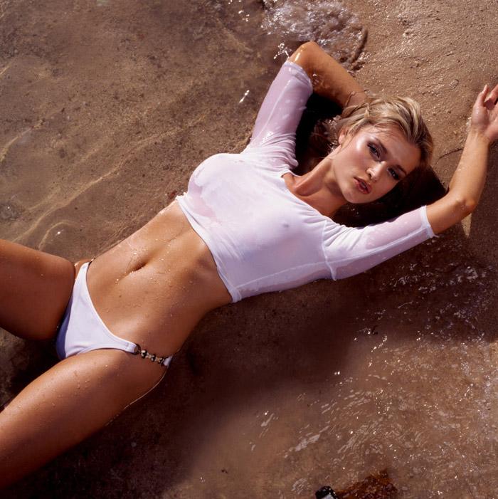Девушка лежит в белой мокрой майке через которую видна голая грудь