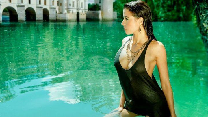 Роковая красотка стоит в водоеме в черной мокрой майке