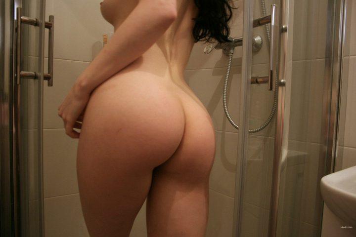 Девушка без комплексов стоит спиной и позирует красивой круглой попочкой