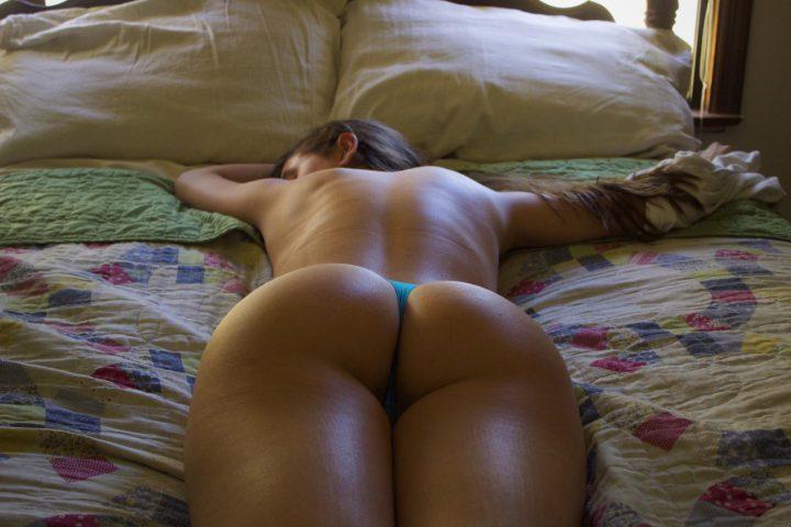 Девушка спит на животе в кровати показав всем круглую упругую попку