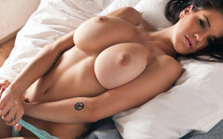 Брюнетка с голыми сиськами лежит на кровати