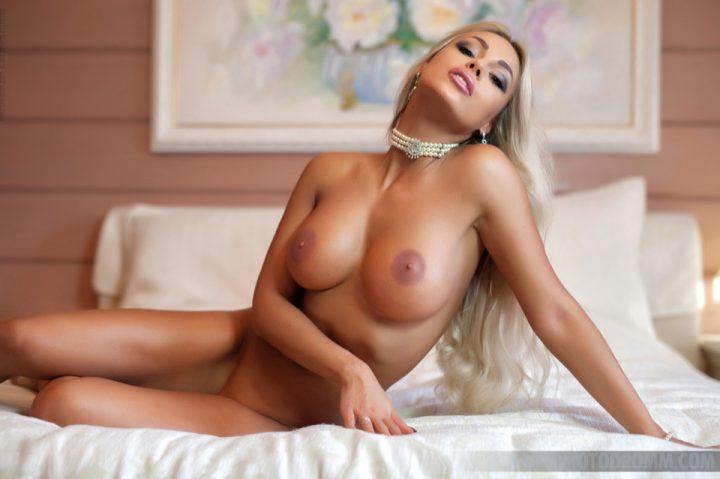 Блондинка с длинными волосами с голой грудью сидит на кровати