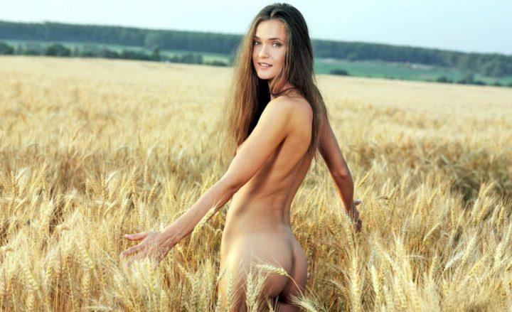 Молодая девушка голышом гуляет по пшеничному полю
