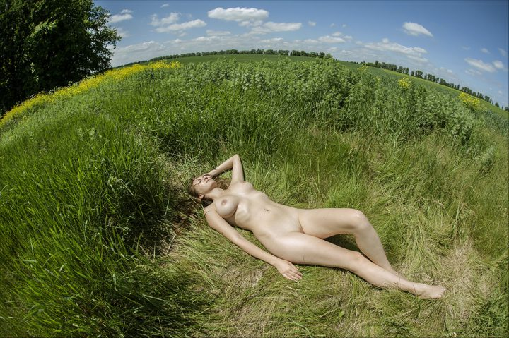 Девушка голая загорает на лугу голая
