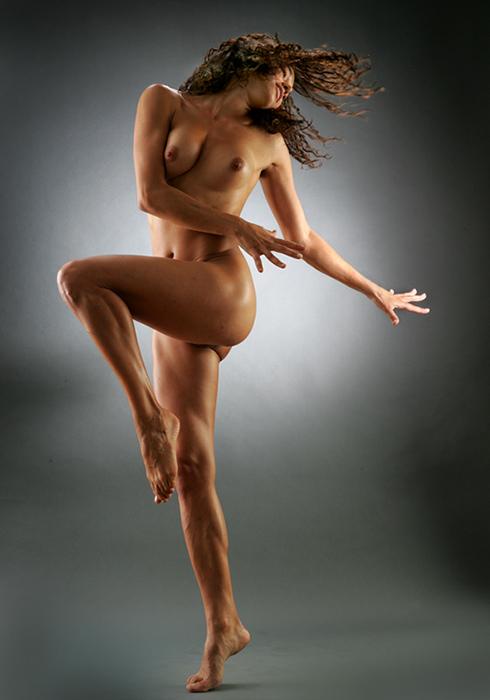 Кудрявая стройная девушка танцует сексуальный танец
