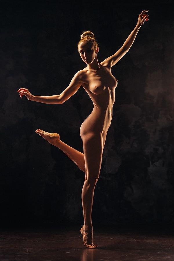 Высокая стройная девушка без одежды сексуально делает па