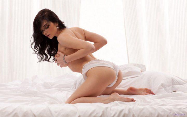 Кудрявая брюнетка в белых трусиках эротично сжала свои сиськи