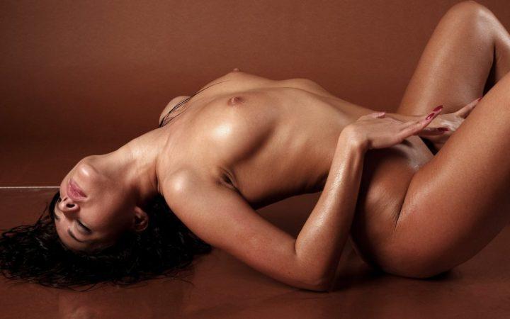 Девушка лежит с закрытыми глазами и эротично выгибается