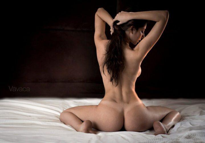 Загадочная девушка сидит на кровати в эротичной позе спиной