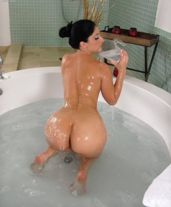 Девушка обнаженная сидит в ванной и поливает себя водой