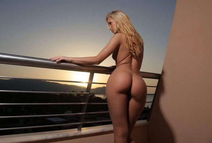 Красивая блондинка стоит на балконе голая с красивой попой