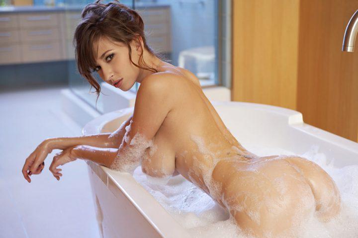 Девушка с красивой прической в ванне с пеной повернулась попой