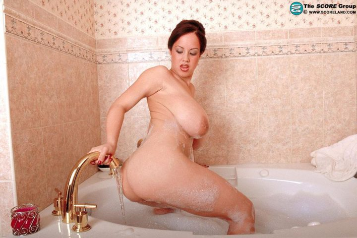 Развратная женщина с большими сиськами моет свою большую попу под струей воды