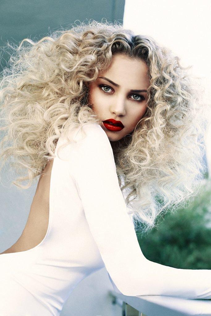 Девушка с красивыми губами, и глубоким взглядом, с шикарной копной белых волос в белоснежном платье с открытой спиной.