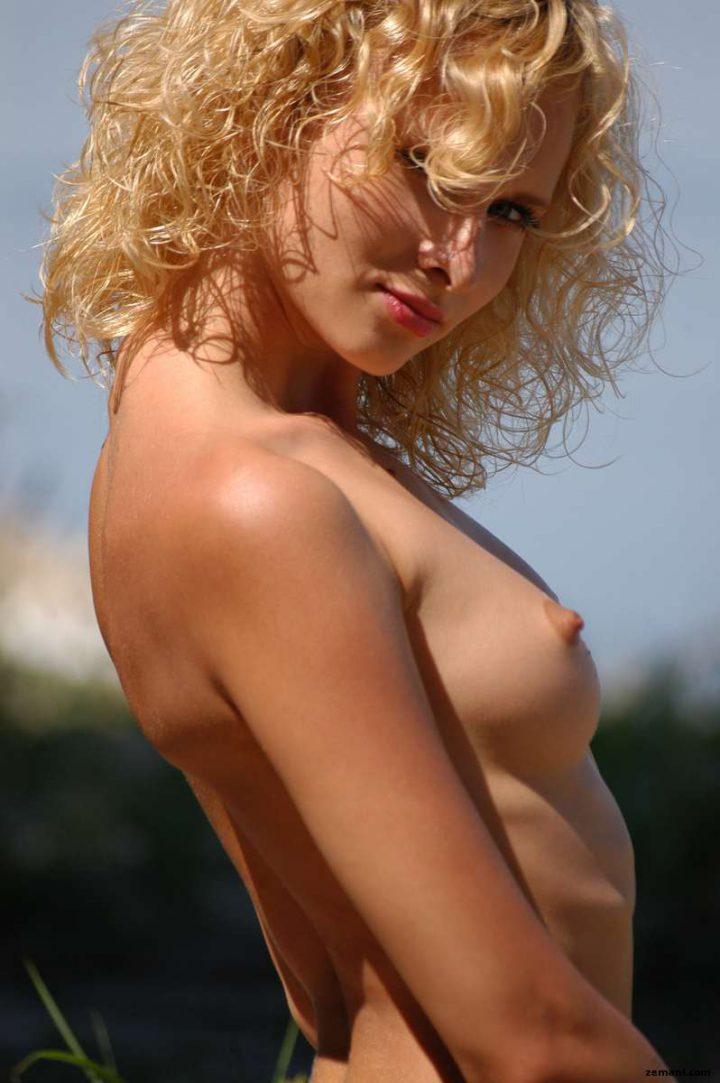 Блондинка с хитрым взглядом и голой грудью стоит в профиль.